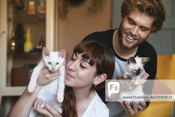 Junges Paar mit Kätzchen zu Hause