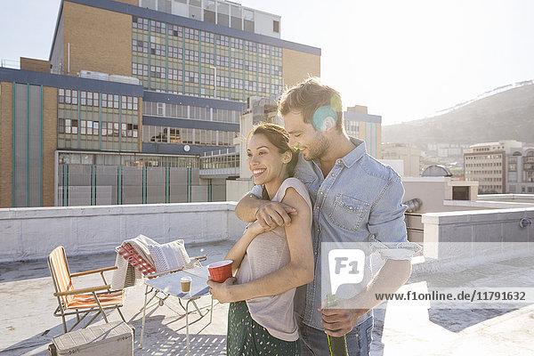 Junges Paar feiert auf einer Dachterrasse  umarmt bei Sonnenuntergang