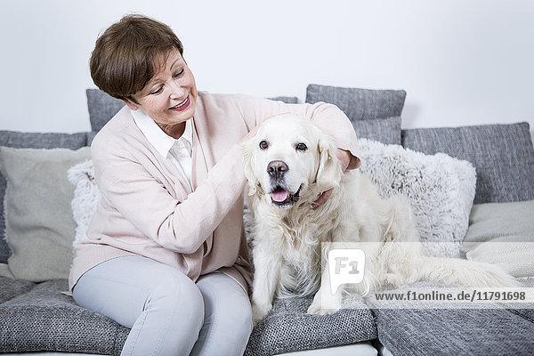 Seniorin auf der Couch sitzend mit ihrem Hund