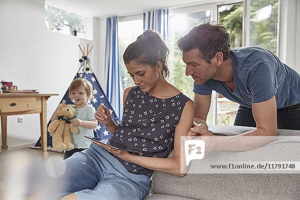 Paar mit Tablette zu Hause mit Junge im Hintergrund