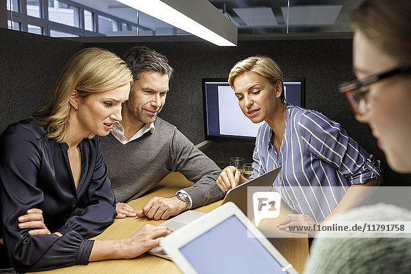 Kollegen mit Laptop und Tablett bei einer Besprechung in der Besprechungsbox