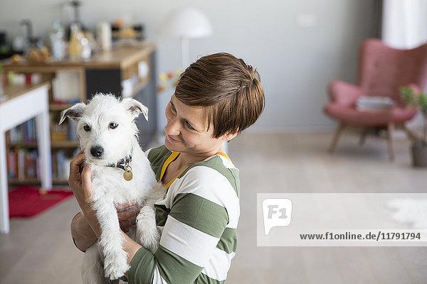 Frau hält Hund auf den Armen zu Hause