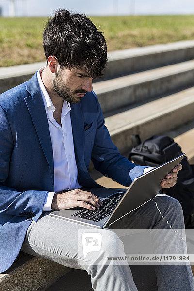 Junger Geschäftsmann sitzt auf der Treppe mit dem Laptop
