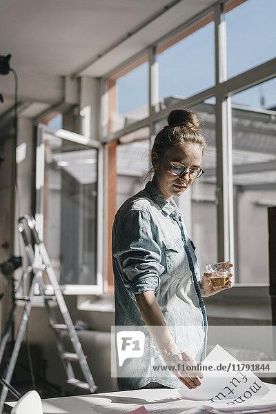 Junge Frau am Tisch bei der Arbeit an Skriptvorlagen