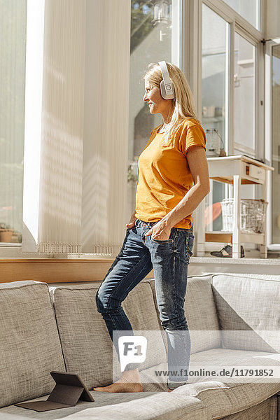 Woman at home standing on couch wearing headphones