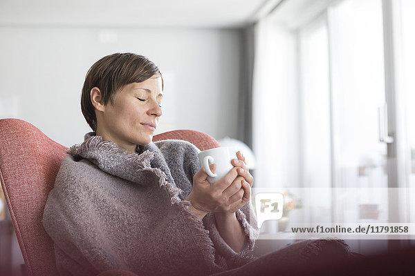 Portrait einer Frau mit geschlossenen Augen  die sich bei einer Tasse Kaffee zu Hause entspannt.