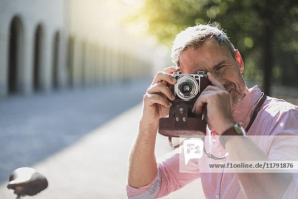 Mann fotografiert mit einer altmodischen Kamera im Park