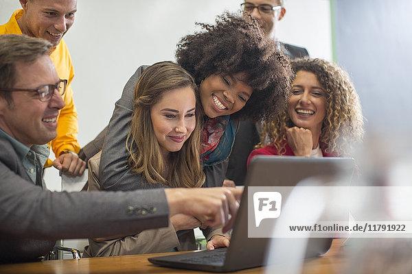 Kollegen im Sitzungssaal teilen Laptop