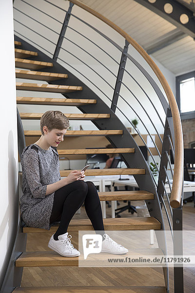 Frau sitzt auf der Treppe im modernen Büro und schaut auf das Handy