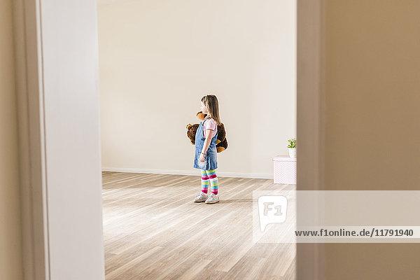 Mädchen in leerer Wohnung mit Teddybär