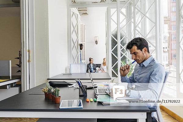 Kaufmann im Büro  Zeitung lesen