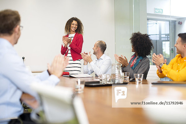 Geschäftsleute applaudieren während einer Sitzung im Sitzungssaal