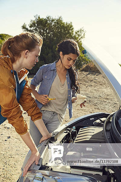 Zwei junge Frauen  die ihr Auto am Straßenrand überprüfen.