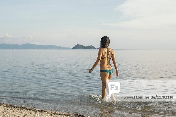 Rückansicht der Frau beim Spaziergang am Meer