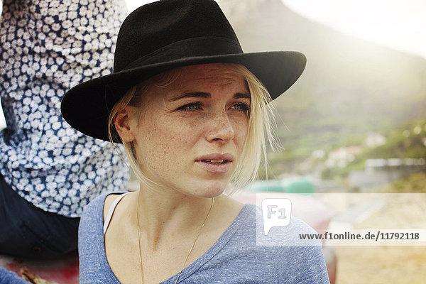 Seriöse blonde junge Frau im Freien mit Blick nach draußen