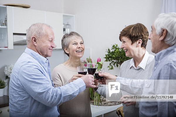 Zwei ältere Paare beim Feiern  Toast mit Rotwein