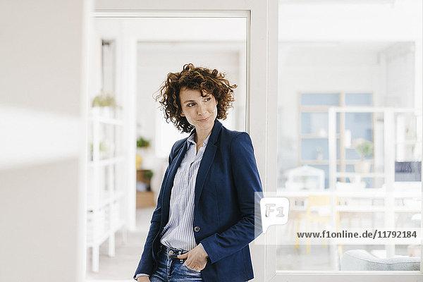 Geschäftsfrau in ihrem Büro stehend  lächelnd