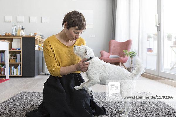 Frau spielt mit ihrem Hund im Wohnzimmer