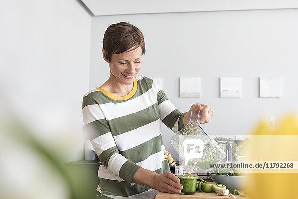 Lächelnde Frau gießt grünen Smoothie in ein Glas