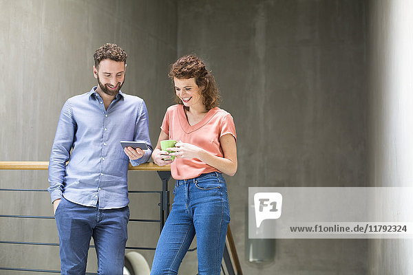 Man and woman in staircase with cell phone and cup of coffee