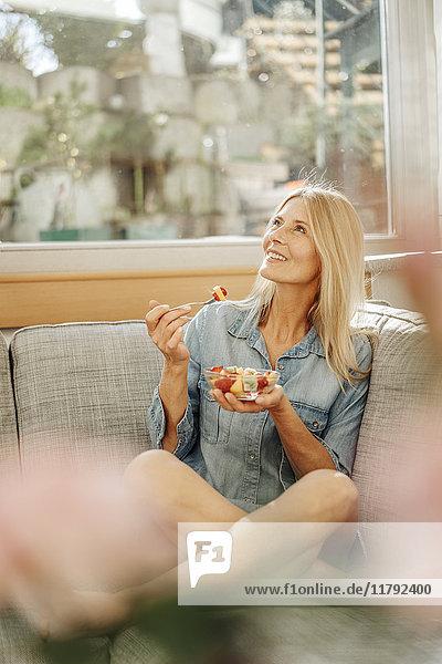 Frau zu Hause sitzt auf der Couch und isst Obstsalat.