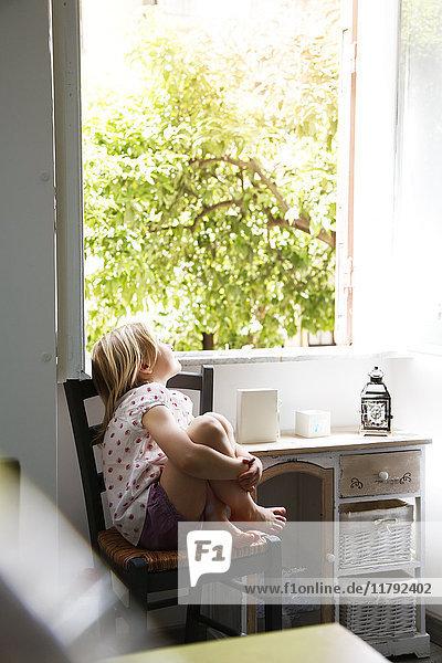 Kleines Mädchen sitzt auf einem Stuhl und schaut aus dem Fenster.