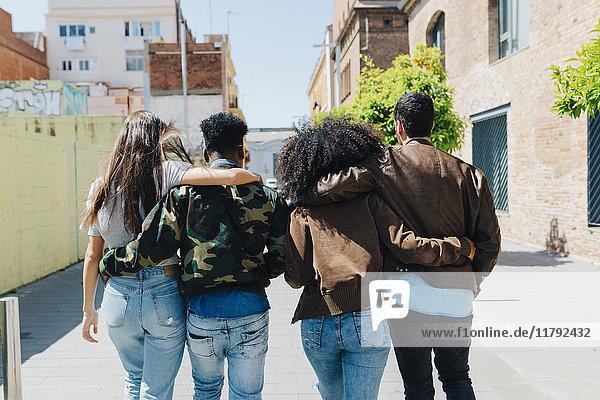 Rückansicht von stilvollen Freunden  die auf der Straße spazieren gehen.