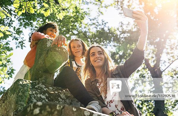 Drei glückliche Mädchen  die mit einem Selfie nach draußen gehen.