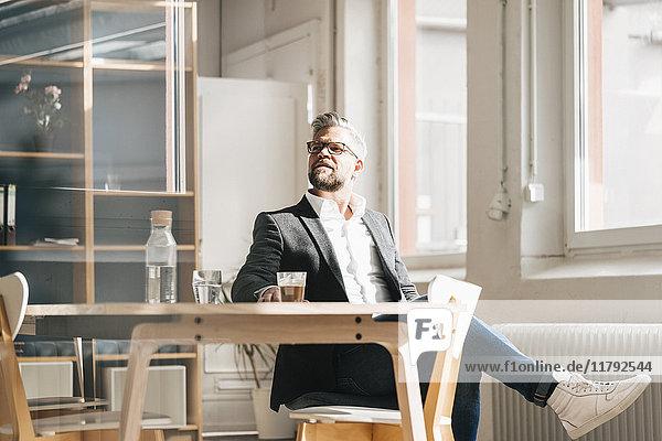 Geschäftsmann sitzt entspannt im modernen Büro