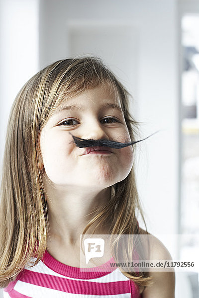Portrait of smiling little girl with moustache