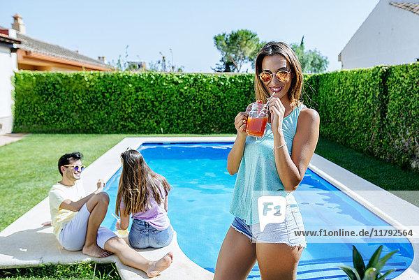 Frau hält einen Drink am Pool mit Freunden im Hintergrund