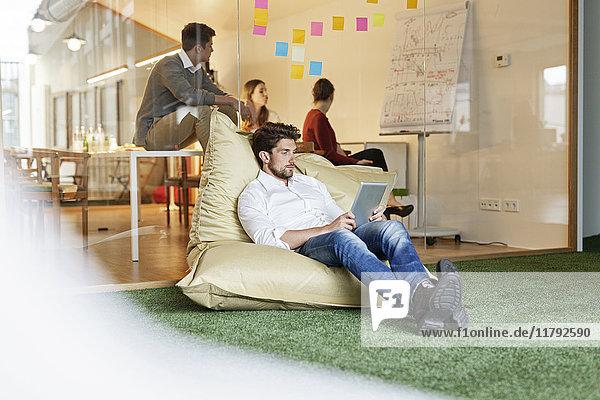 Mann im Büro mit Tablette im Bohnenbeutel mit Besprechung im Hintergrund