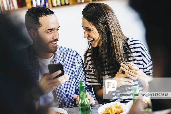 Happy couple sharing cell phone at dining table