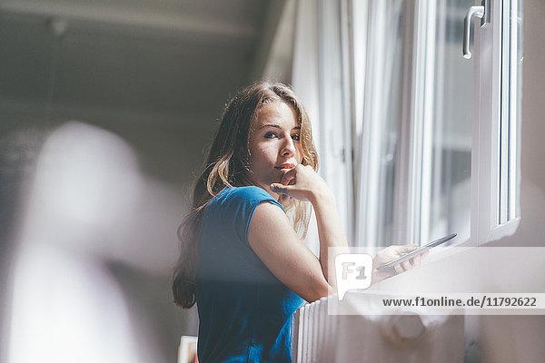 Porträt einer jungen Frau am Fenster