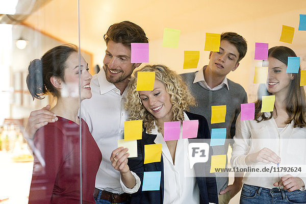 Business people discussing in front of glass screen with sticky notes