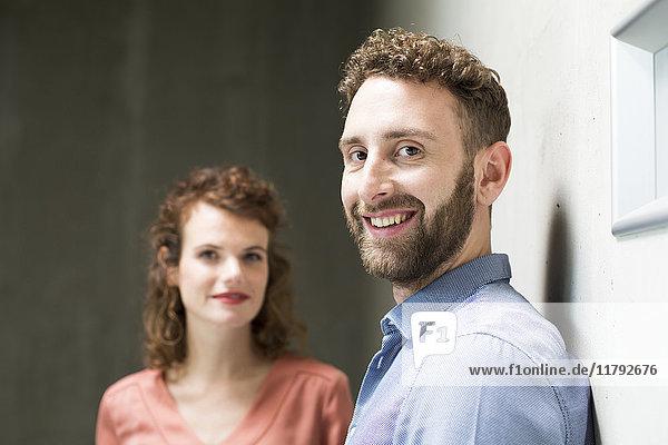 Porträt des lächelnden Mannes mit Frau im Hintergrund