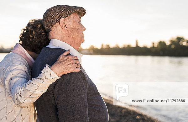 Glückliches Seniorenpaar am Strand bei Sonnenuntergang