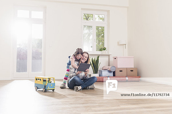 Glückliches Mädchen und Mutter mit Tablette in leerer Wohnung