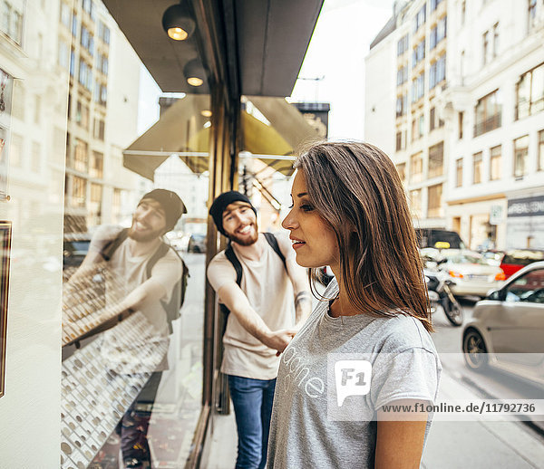 Young woman looking fascinated in shop window  boyfriend trying to pull her away