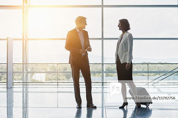 Geschäftsmann und Geschäftsfrau beim Gespräch am Flughafen im Gegenlicht