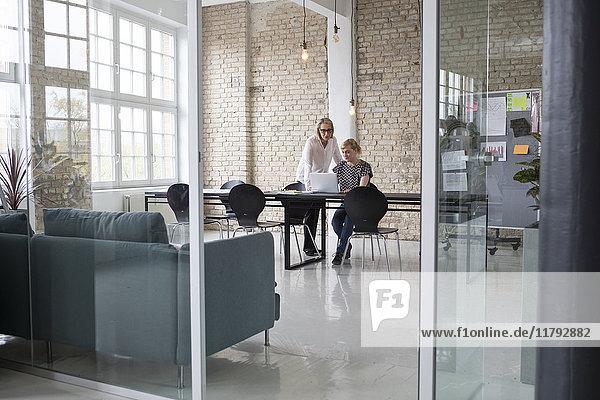 Reife Geschäftsfrau  die mit einer jüngeren Kollegin im Büro arbeitet.