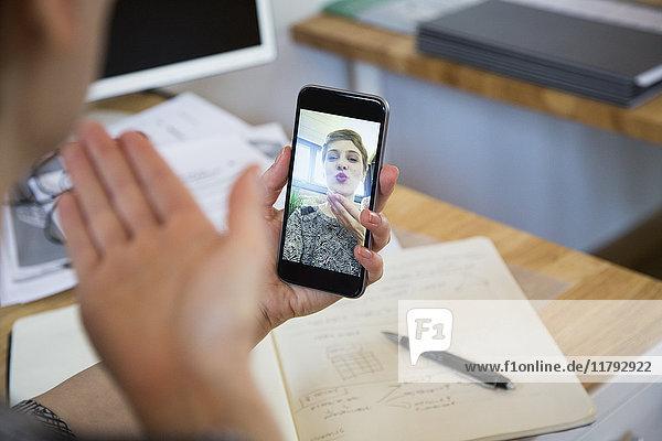 Nahaufnahme einer Frau am Schreibtisch mit einem Selfie
