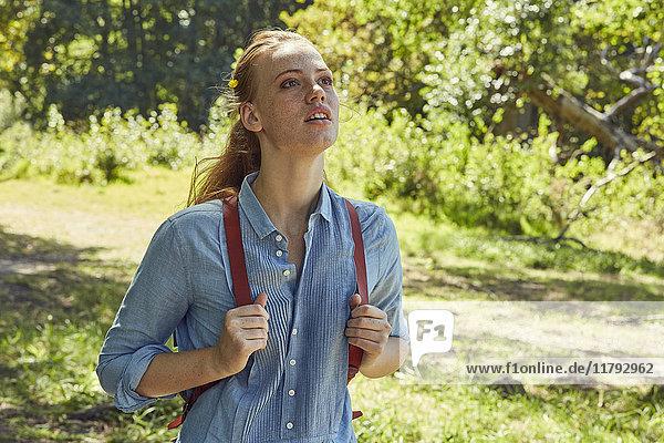 Porträt einer jungen Frau in der Natur  die etwas beobachtet.