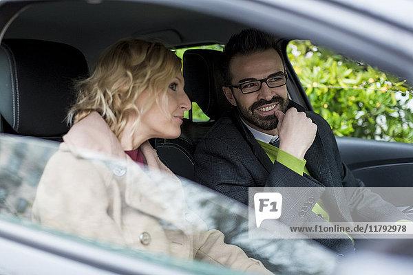 Lächelnder Geschäftsmann und Geschäftsfrau im Auto