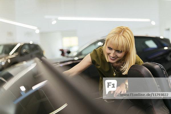 Blonde Frau betrachtet Cabriolet im Autohaus