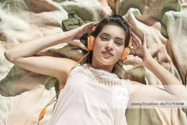 Porträt einer jungen Frau  die auf einer Decke liegt und Musik mit Kopfhörern hört.