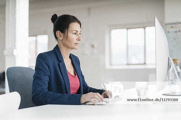 Frau arbeitet am Schreibtisch in einem Loft