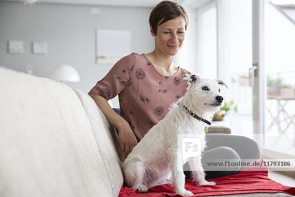Frau und ihr Hund sitzen zusammen auf der Couch.