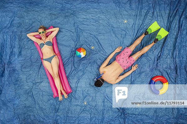 Mann schnorchelt im Meer  während die Frau sich auf dem Luftmatratzenbett ausruht.