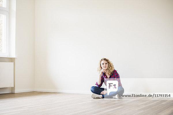 Junge Frau im neuen Zuhause auf dem Boden sitzend